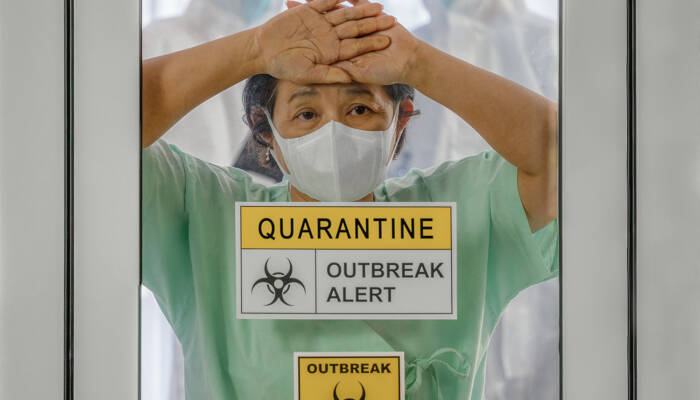 covid-19 infected patient in quarantine room with quarantine and breakout alert sign at hospital with blurred disease control experts inside