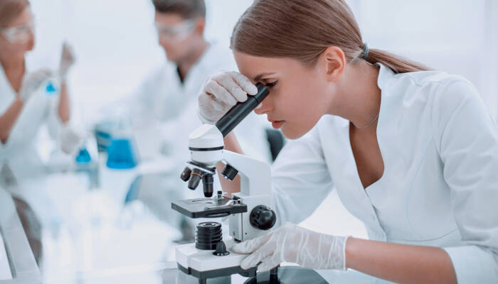 close up. female scientist using a microscope in a chemical laboratory